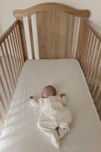 Noworodek w szerokim, pustym łóżeczku, leżący na plecach, śpi.