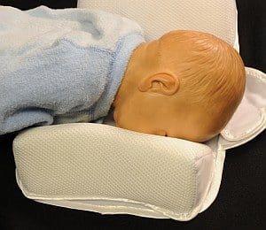 Dziecko twarzą w dół - manekin - umieszczone w pozycjonerze.