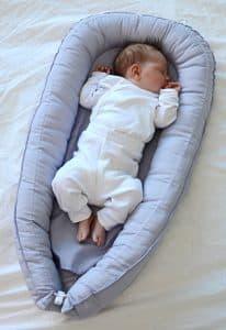 Dziecko z główką na bok, z nosem i buzią tuż obok grubej ściany gniazdka niemowlęcego.